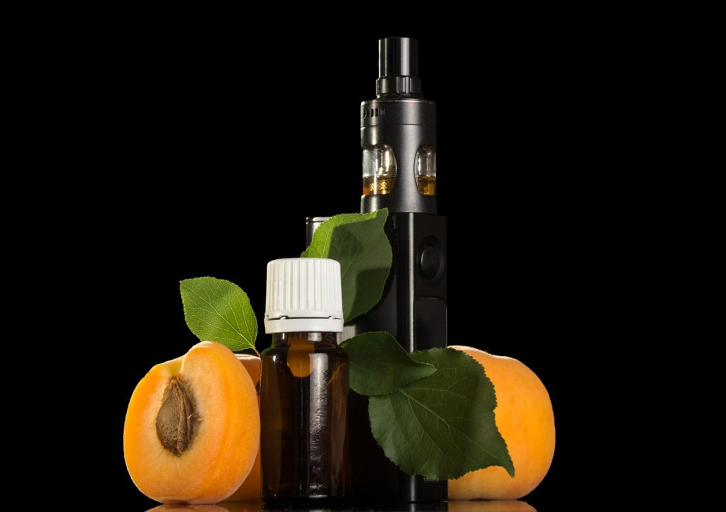 Fluid with apricot flavor and electronic cigarette isolated on black