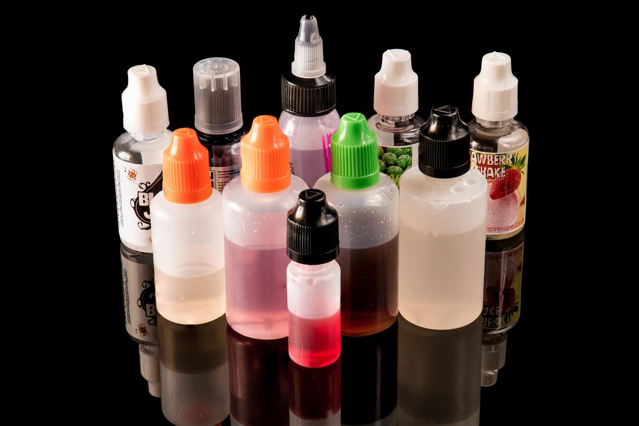 E-liquid plastic bottles on a black backdrop