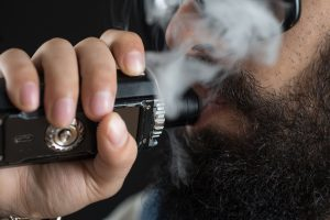 Close up of an unrecognizable young man smoking from a vaporizer