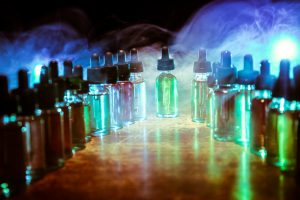 Smoke clouds and vape liquid bottles on dark background. Light effects. Useful as background or vape advertisement or vape background. Selective focus