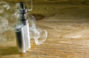 Electronic cigarette shrouded in steam standing on a wooden table