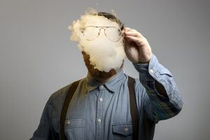 portrait of a man who is smoking an e-cigarrette